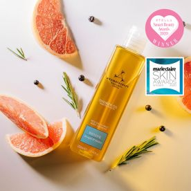 Revive Shower Oil with grapefruit slices, rosemary and juniper berries on a white background